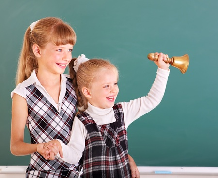 Happy schoolchildren in classroom near blackboard. photo