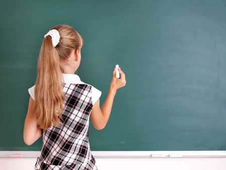 Happy schoolchild writing on blackboard. Stock Photo - 10300947