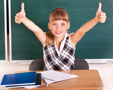 Happy schoolchild in classroom near blackboard. photo