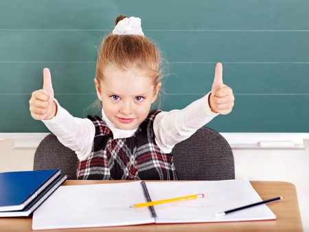 Happy schoolchild in classroom near blackboard. Stock Photo - 10292538