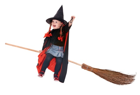 Little girl in costume Halloween witch in black dress and hat fly on broom.Isolated. photo