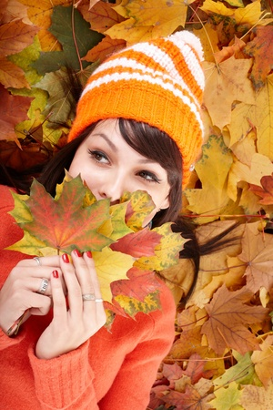 Young woman in autumn orange leaves. Outdoor. Stock Photo - 10533120