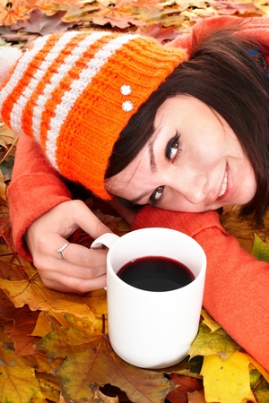 Girl in autumn orange leaves with cup coffe. Outdoor. photo