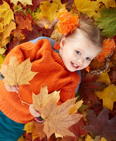 Little girl in autumn orange hat on leaves and gift box. Outdoor. photo