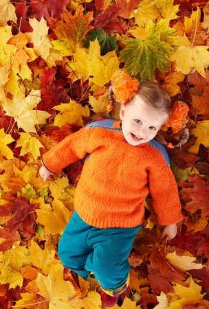 Little girl in autumn orange leaves. Outdoor. photo