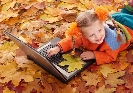 Little girl in autumn orange leaves with laptop. Outdoor. photo
