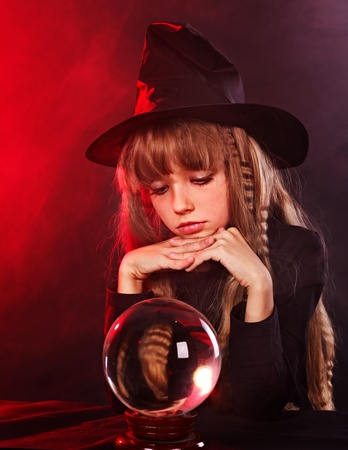 Little girl witch holding crystal ball. photo