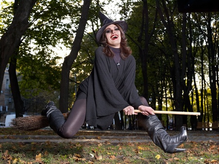 Young beautiful witch fly on broomstick outdoor. photo
