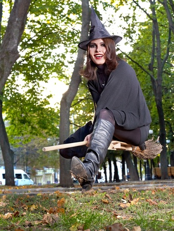 broomstick: Young beautiful witch fly on broomstick outdoor.