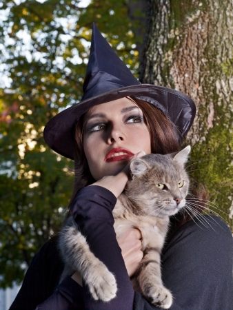 demoniacal: Young beautiful witch holding cat outdoor. Stock Photo