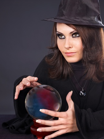 Young  beautiful woman with crystal ball. Fortune telling. Stock Photo - 10533138