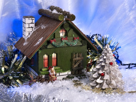 Still life with christmas decoration. House with chimney and Santa Claus. photo