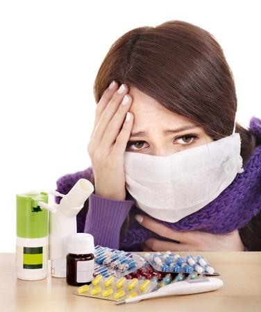 femme masqu�e: Jeune femme ayant la grippe prend des pilules. Banque d'images