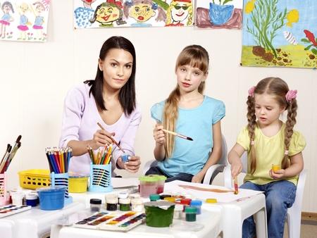 maestra preescolar: Pintura infantil en edad preescolar. Maestro ayudar ni�a. Foto de archivo