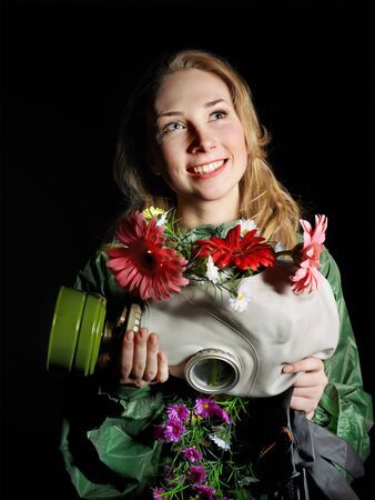Young woman holding flowers and gas mask . Stock Photo - 10533484