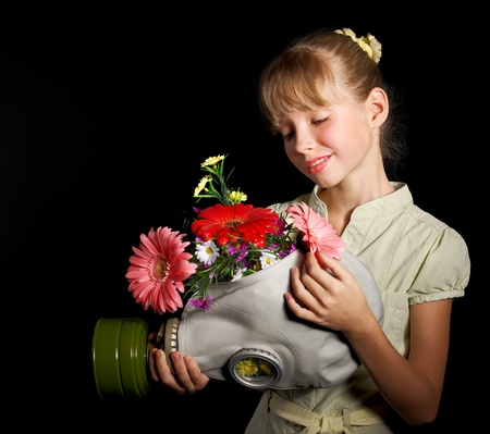 Little girl holding flowers and gas mask . Stock Photo - 10533262