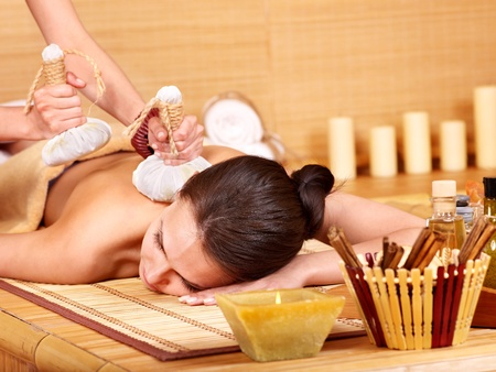 compress: Young woman getting massage in bamboo spa.