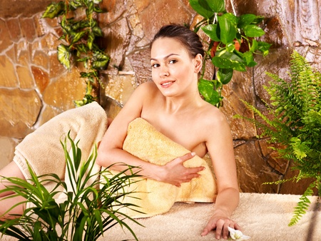 ferns and orchids: Beautiful young woman getting massage in spa. Stock Photo