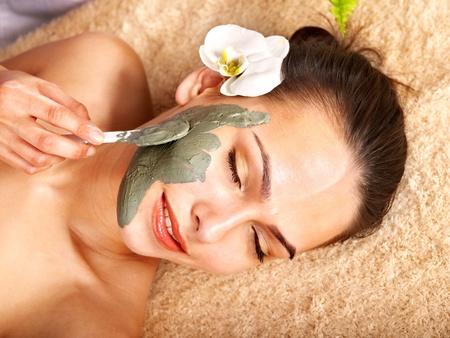 facial massage: Belle fille ayant un masque � l'argile s'appliquent par esth�ticienne.