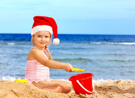 Child in santa hat playing on  beach. Summer New Year. photo