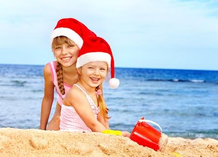 beach happy new year: Children in santa hat playing on  beach. Summer New Year.