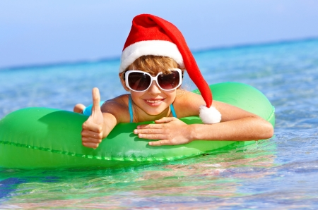 Child in santa hat  floating on inflatable ring in sea. Thumb up. Фото со стока
