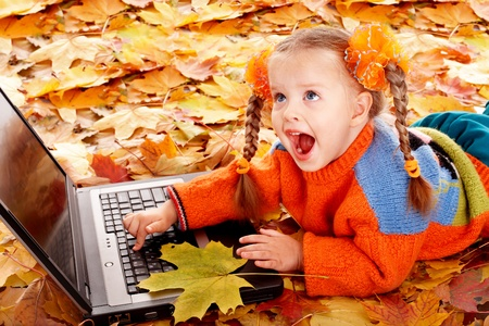 Girl child in autumn orange leaves with laptop. Outdoor. photo