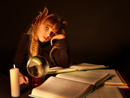 foretell: Child reading magic book at candle. Fortune telling Stock Photo