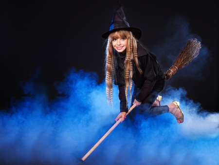 Girl in witchs hat flying on broomstick. photo