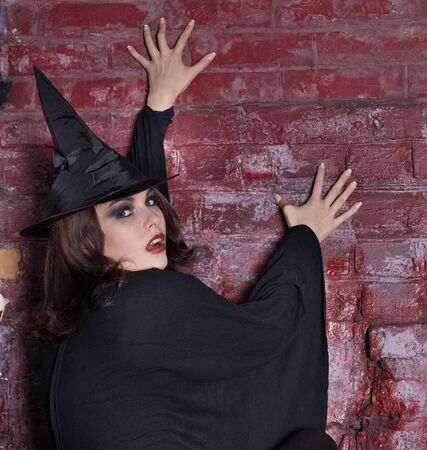 demoniacal: Brick wall portrait of young woman. Halloween witch. Stock Photo