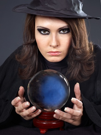 Young  beautiful woman with crystal ball. Fortune telling. photo