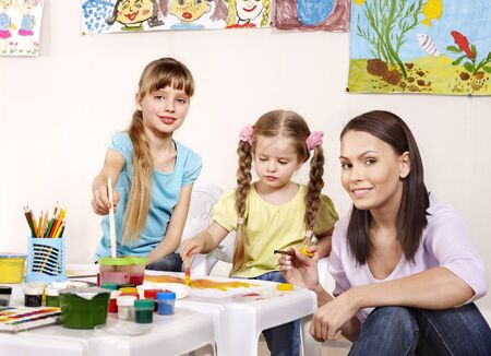 Child painting in preschool. Teacher help by little girl. photo