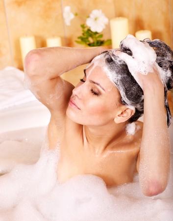 Woman washing hair in bubble bath. Stock Photo