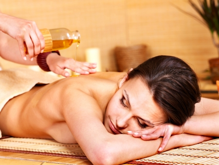 back massage: Young woman getting massage in bamboo spa.