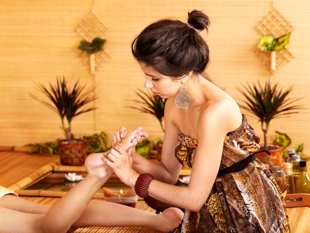 Young woman getting foot massage in bamboo spa. (massage,\ reflexology, thai)