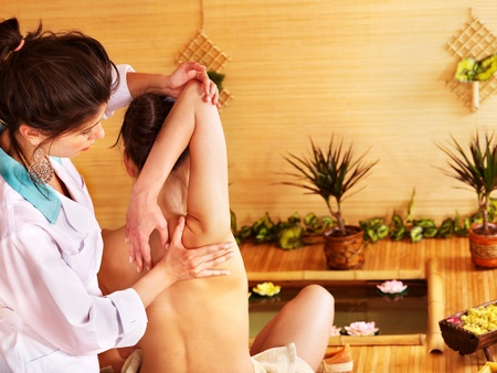 thai massage: Young woman getting massage in bamboo spa..