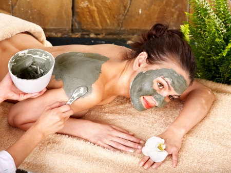 clay: Beautiful girl having clay body mask apply by beautician.