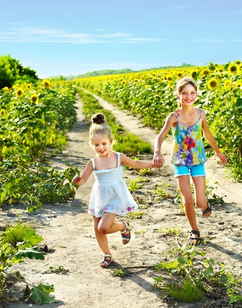 Group children running across sunflower field outdoor.  photo