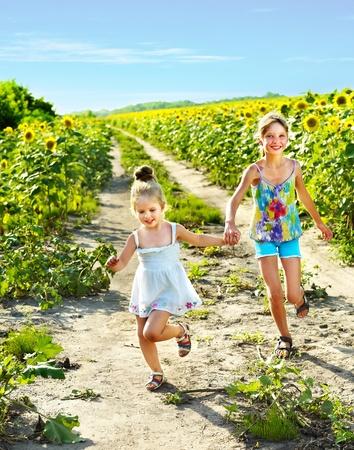 across: Group children running across sunflower field outdoor.  Stock Photo