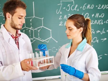 examenes de laboratorio: Estudiante de química de grupo con el matraz en el aula.