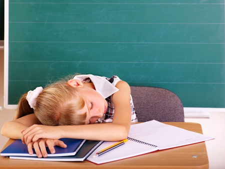 fatigued: Happy schoolchild in classroom near blackboard.