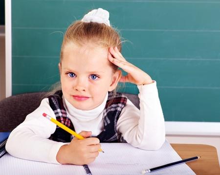 schoolroom: Happy schoolchild in classroom near blackboard.