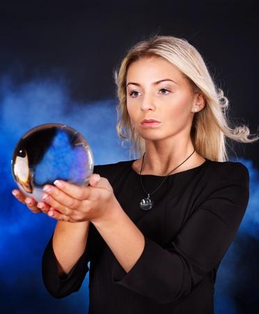 Joven mujer hermosa con una bola de cristal.