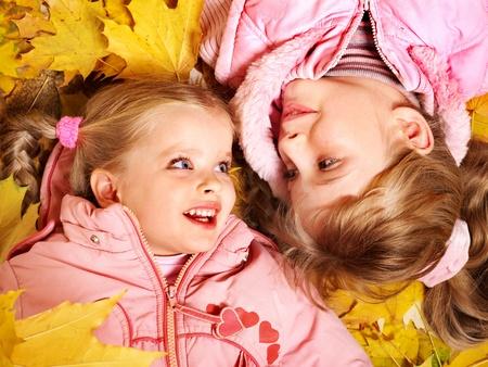only girls: Children in autumn orange leaves. Outdoor.