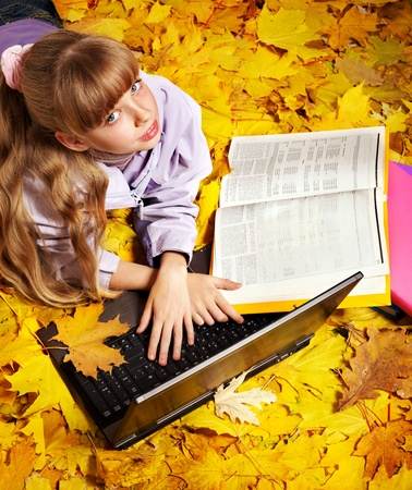 Childl in autumn leaves with laptop and books. Outdoors. photo