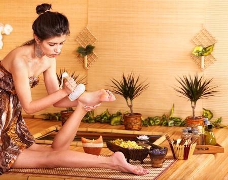 reflexologie: Jeune femme se massage des pieds dans le spa de bambou.