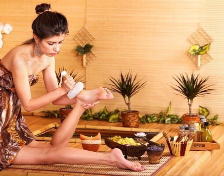 pampering: Young woman getting foot massage in bamboo spa.