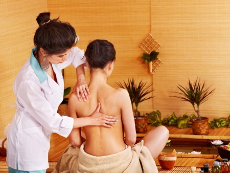 thai orchid: Young woman getting massage in bamboo spa..