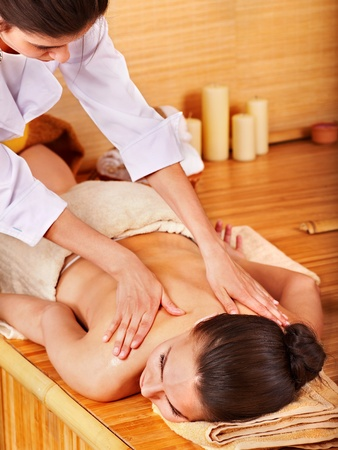 Young woman getting massage in bamboo spa. photo