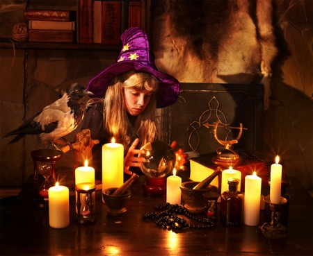 divining: Witch  child with crystal ball. Halloween. Stock Photo